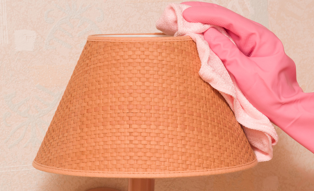 A lamp shade being wiped off.
