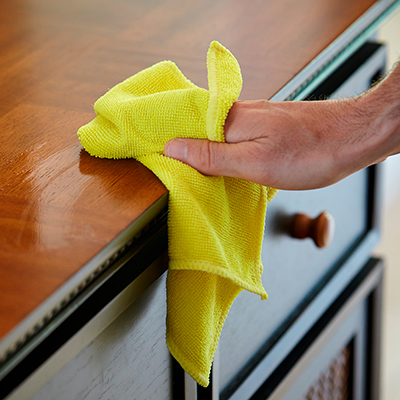 A person cleaning a counter with a microfiber cloth.