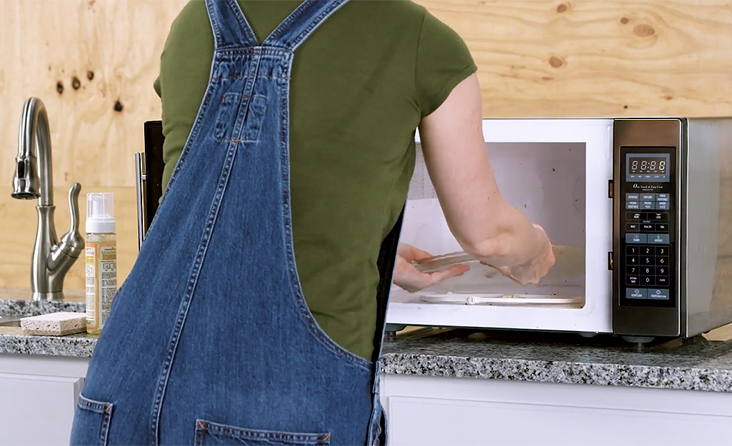 A woman removing the glass tray from the microwave interior.