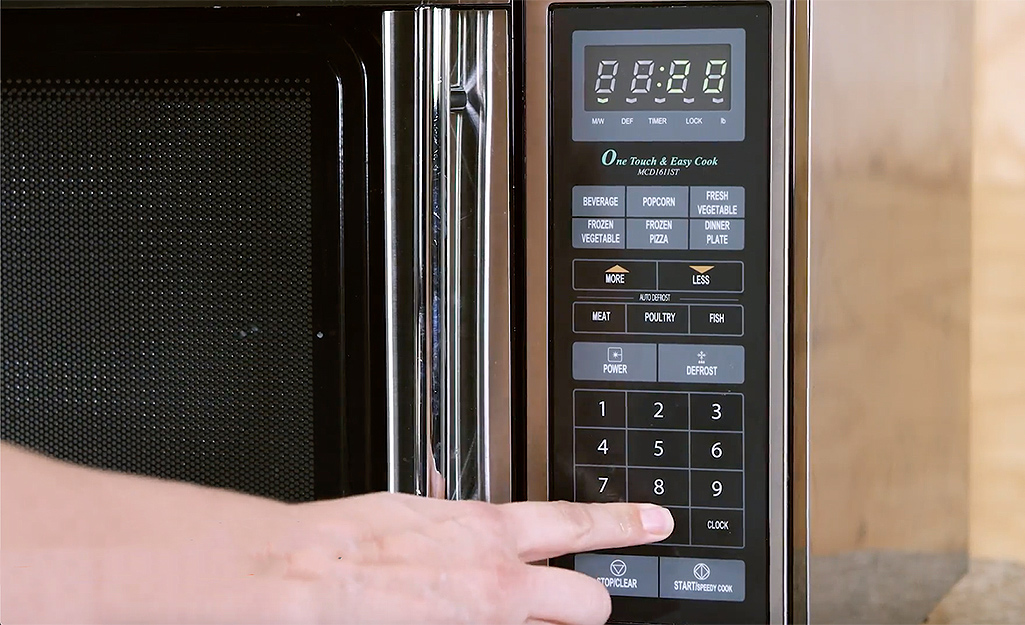 A woman sets the microwave to heat up for several minutes.
