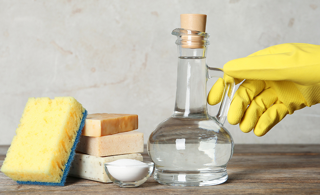 A hand in a dishwashing glove reaches for a clear bottle of vinegar that sits next to baking soda, soap and a sponge.