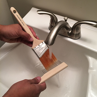 A person uses a brush comb to clean a paint brush under running water.