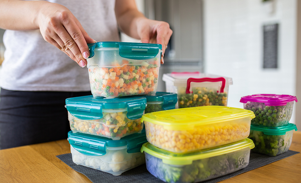 A person places refrigerated food containers on a kitchen counter.