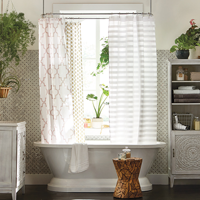 White patterned shower curtains hang in a bathtub shower in a white bathroom.