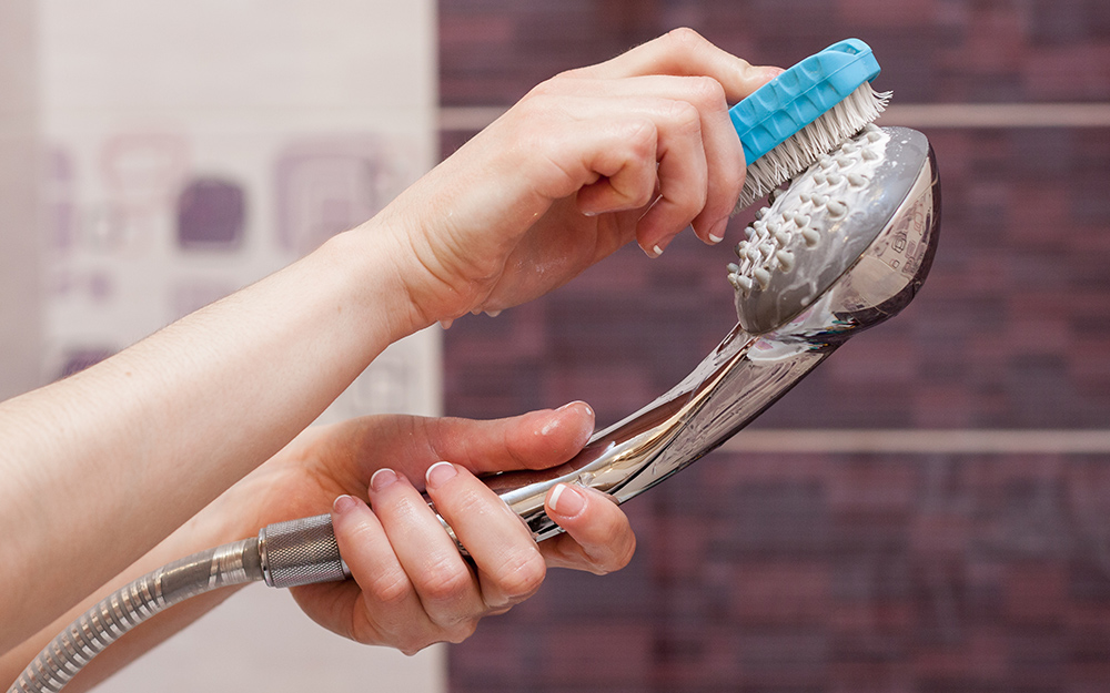 A person cleaning a handheld shower head with a scrub brush