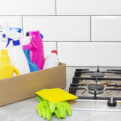 Cleaning products beside a stove top.