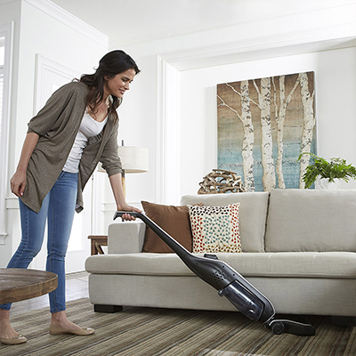 A woman using a vacuum cleaner on a living room rug