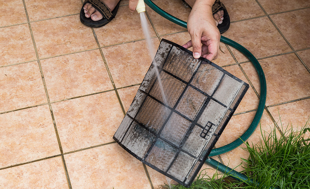 A person uses a garden hose to clean an air filter.