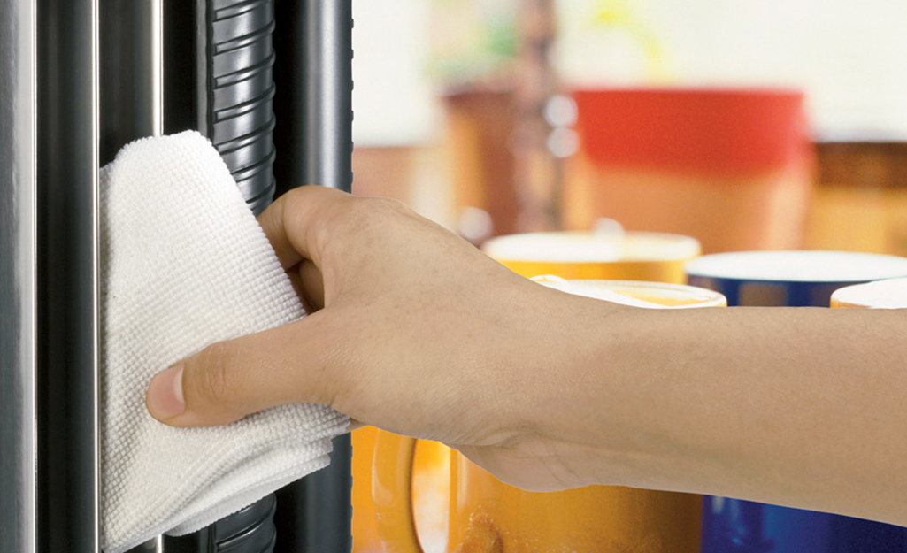 A person wiping down an air purifier with a microfiber cloth.