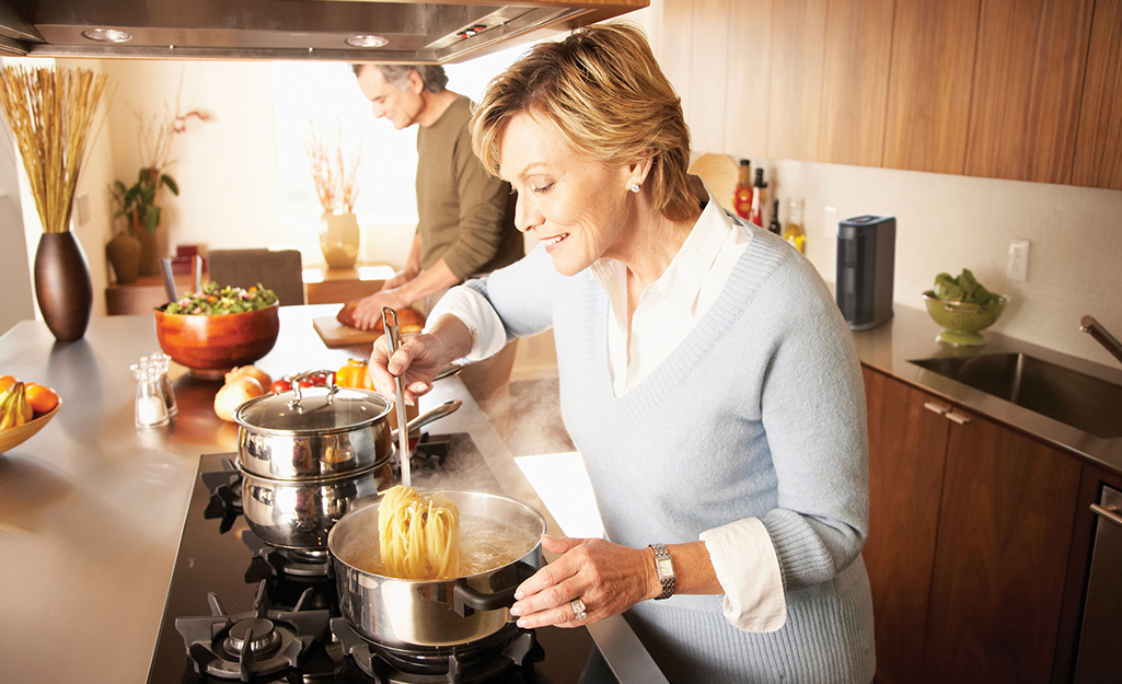 A couple cooks in a kitchen with an air purifier.