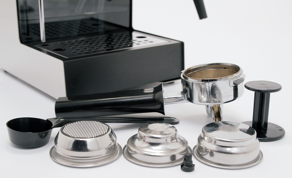 A black-handled portafilter and other components stand alongside an espresso machine.