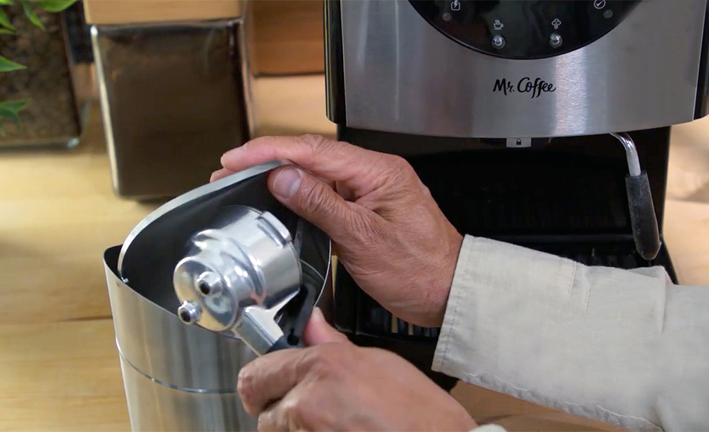 A person empties the portafilter while cleaning an espresso machine.