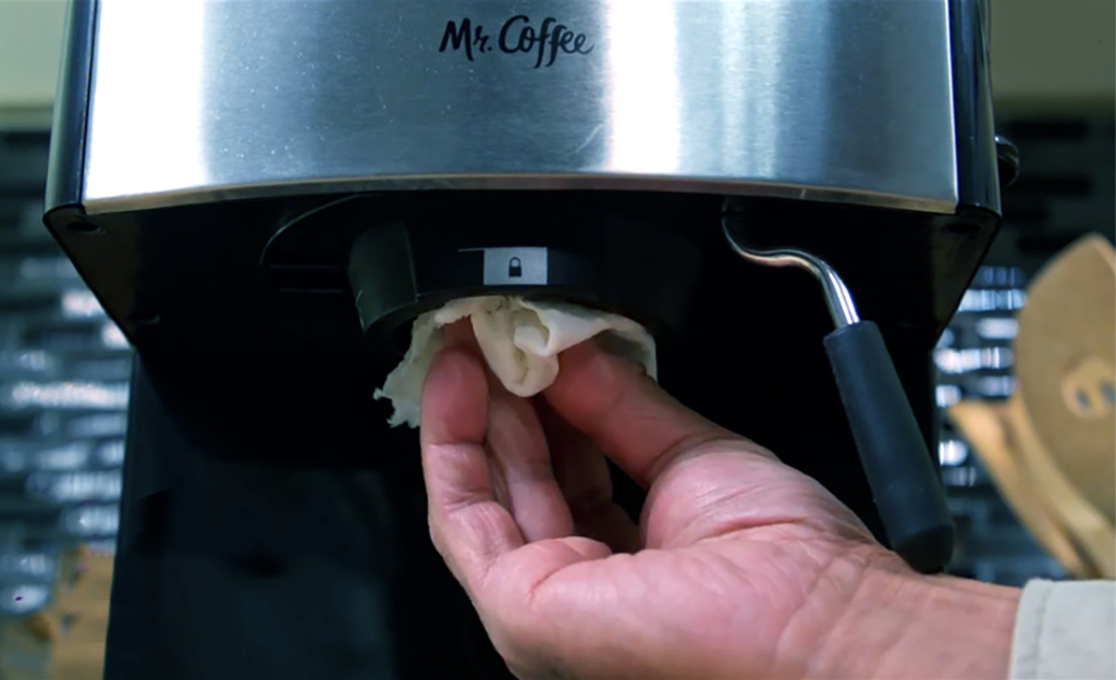 A person uses a cloth to wipe the gasket of the group head of an espresso machine.