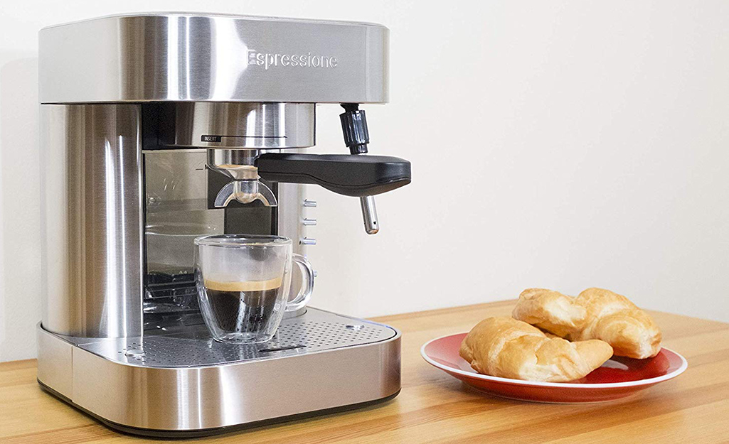 A fresh shot of espresso stands in an espresso maker next to a plate of croissants.