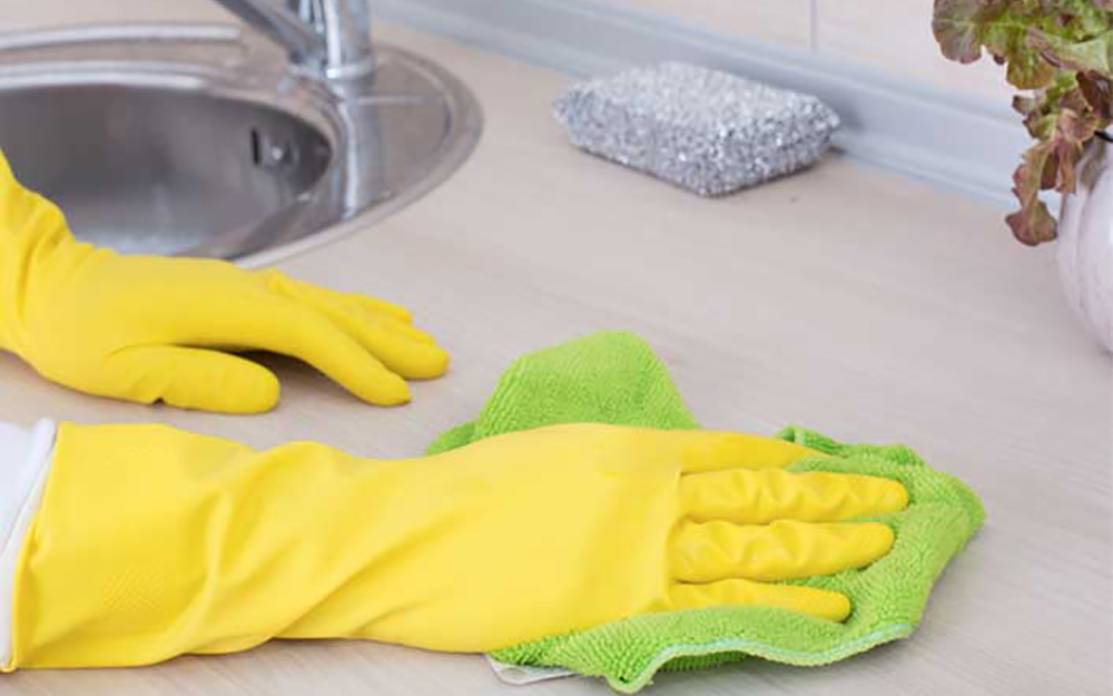 A person cleaning a counter with a rag while wearing gloves