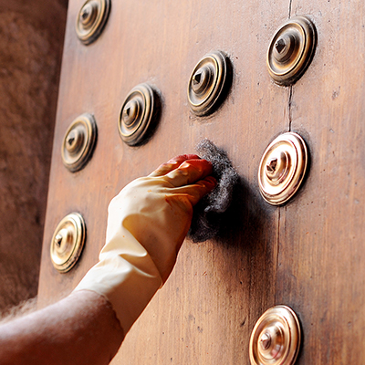 A person cleaning brass accents on a wooden door.