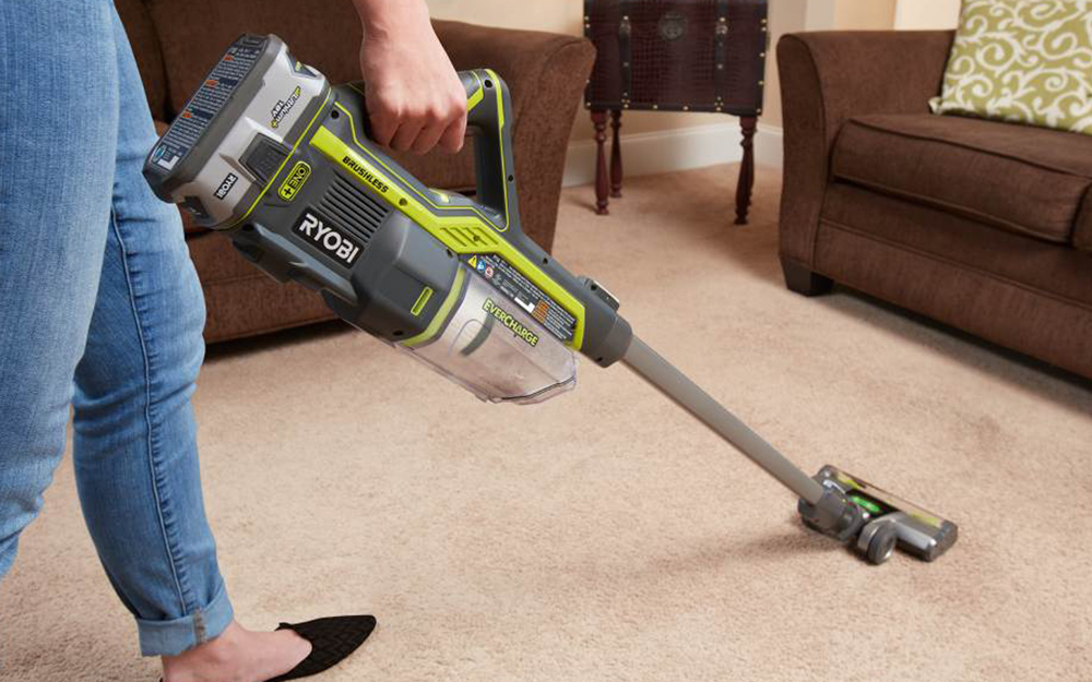 Woman vacuuming carpet before steam cleaning it.