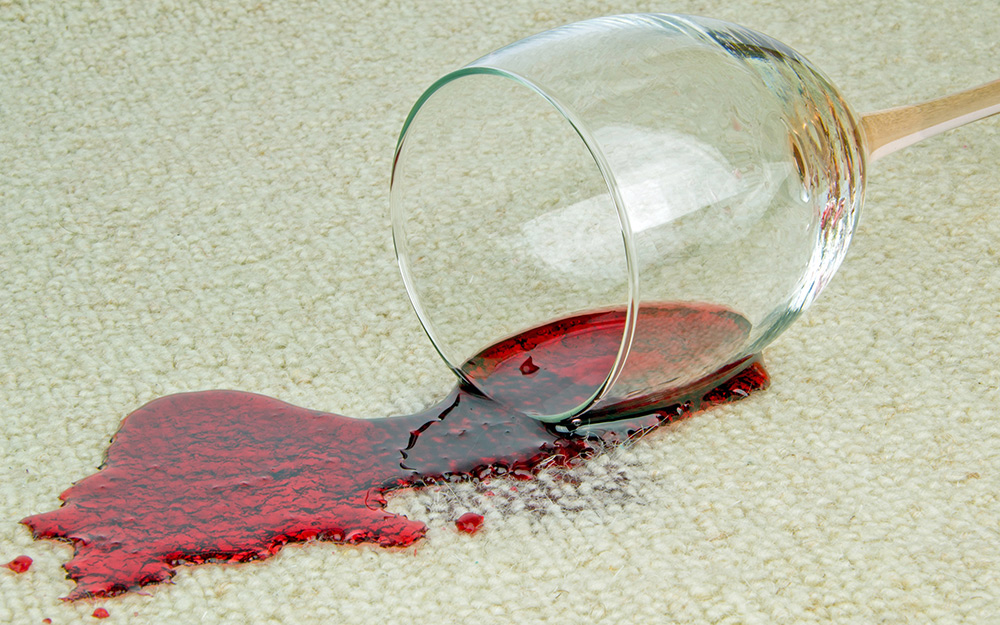 A glass of red wine is spilled on carpet.