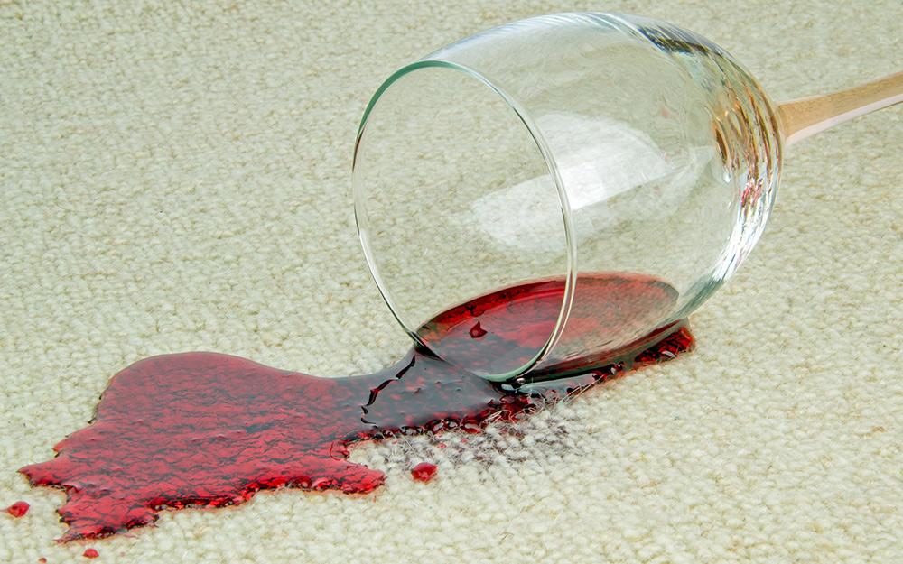 Một ly rượu vang đỏ bị đổ trên thảm.