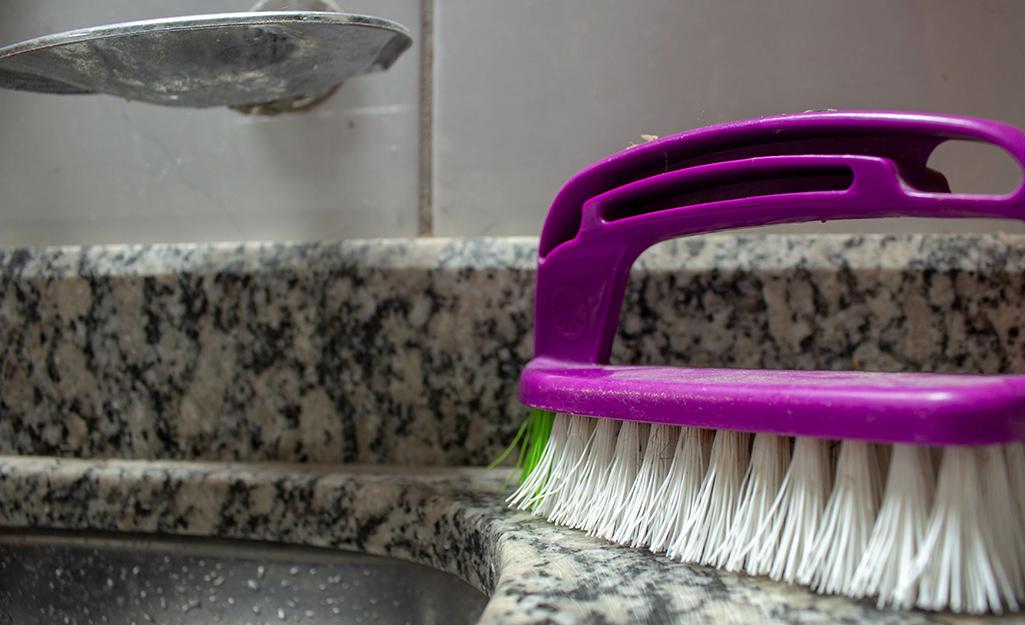 Scrub brush sitting on a granite countertop.