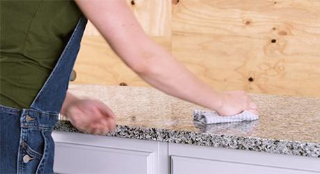 Person wiping granite countertop.