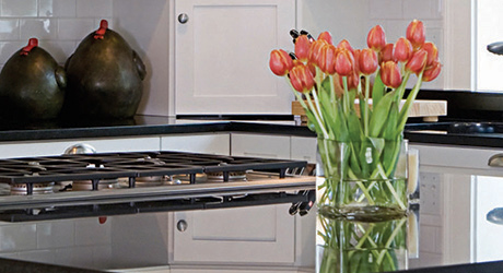 A vase of red tulips sitting on top of a clean kitchen countertop.