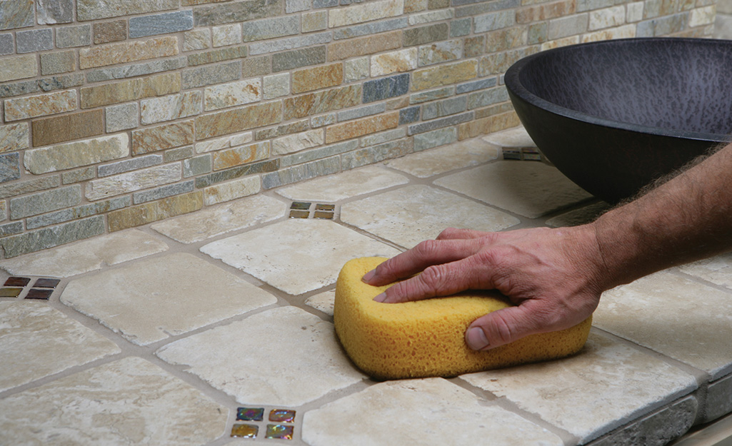 Someone cleaning grout on a tiled floor with a sponge.