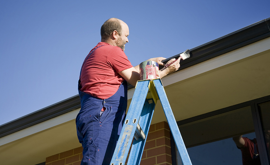 A man on a ladder painting gutters.