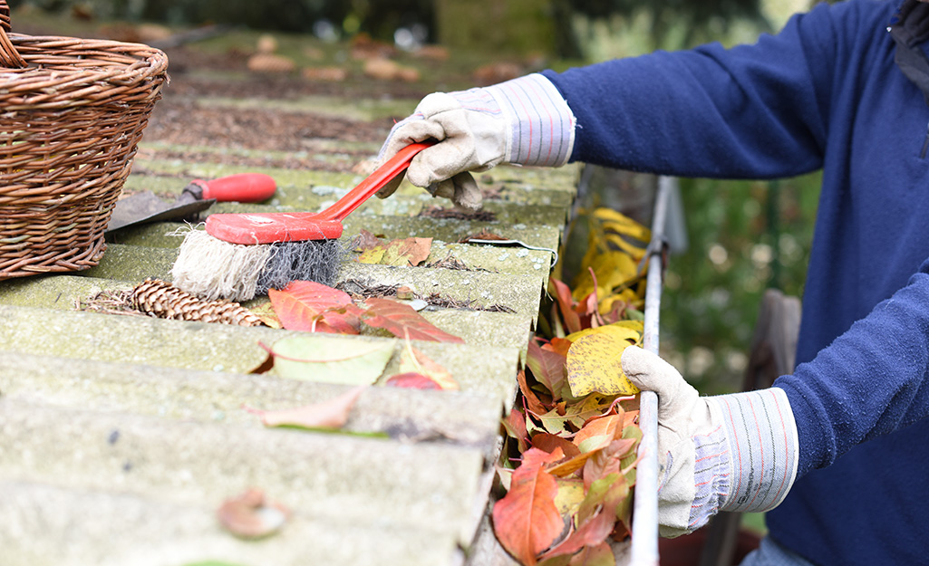 A person cleaning leaves from gutters.