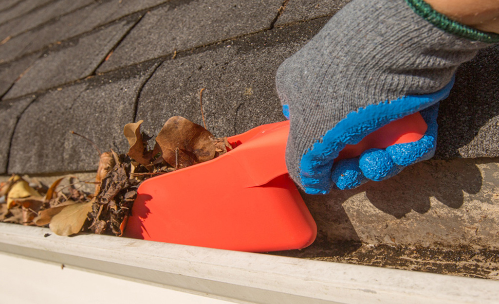 Person with orange scoop cleaning leaves out of gutters.