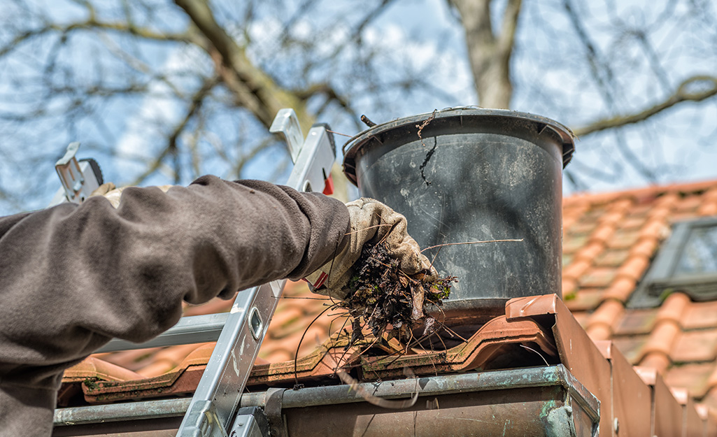 A person removing leaves from a gutter.