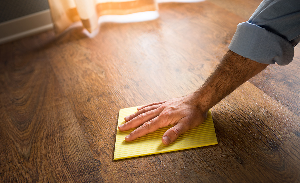 A person buffing out scratches on a wood floor.