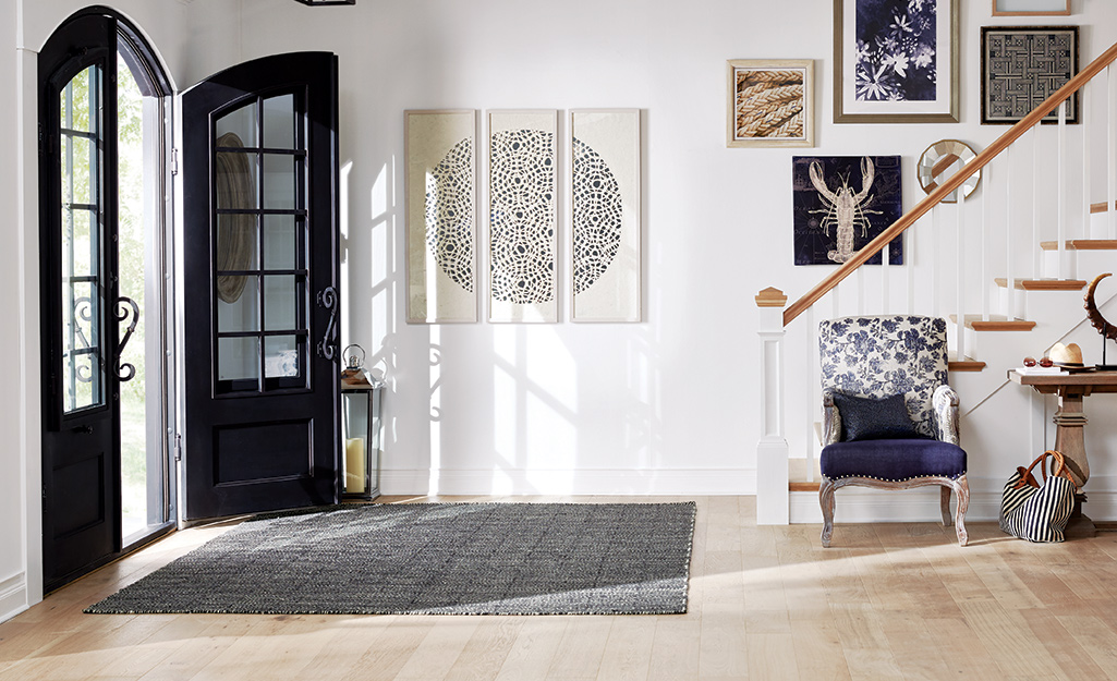 A rug covers the hardwood floor between the entrance and a staircase.