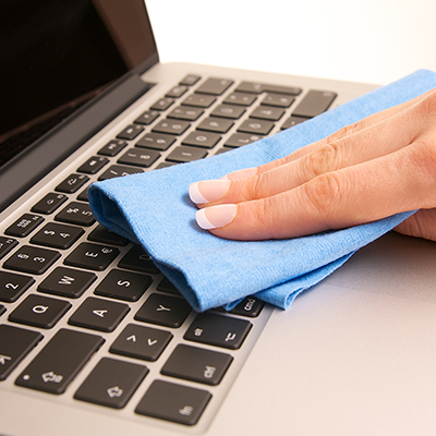 A person wiping a laptop keyboard with a microfiber cloth.