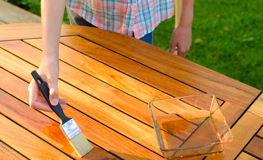 Two people preparing to clean an outdoor table with a water pail on top of it.