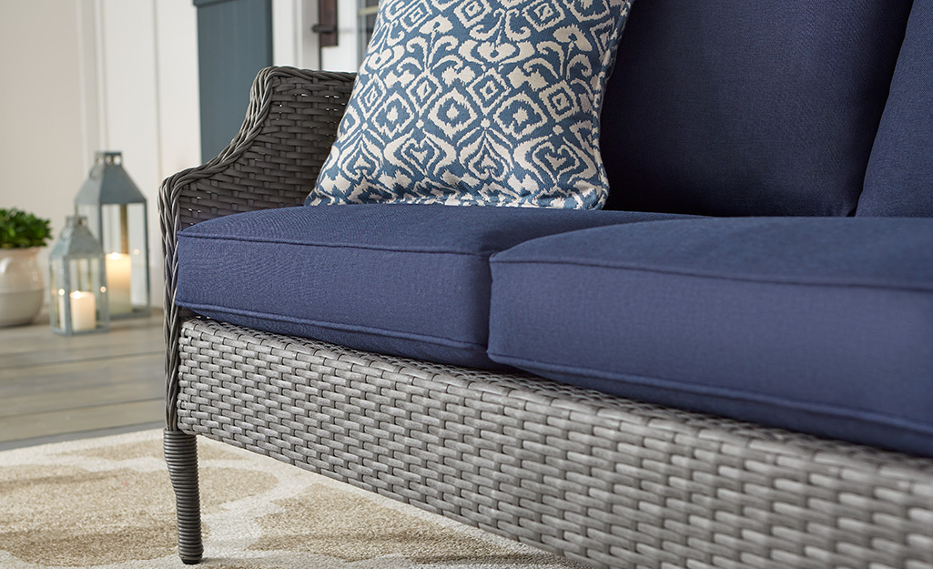 An outdoor sofa with clean cushions on a patio.