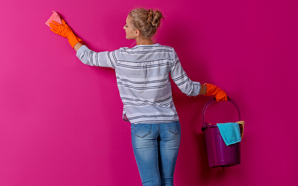 A person washes a wall with a sponge while holding a bucket.