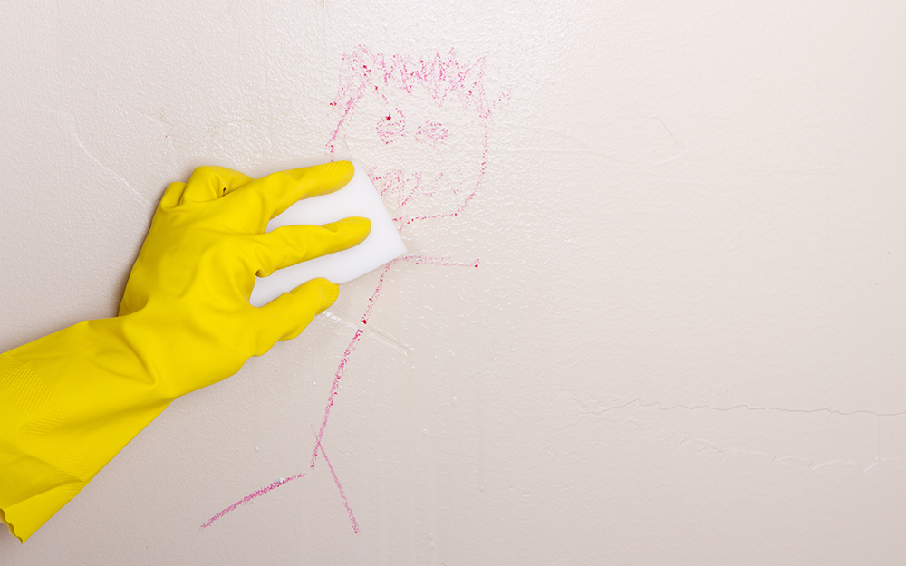 A person wearing gloves uses an erasing pad to clean a crayon drawing from a wall.