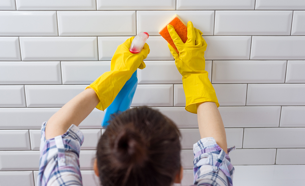 Someone spraying a cleaning solution onto tile and wiping it with a sponge.