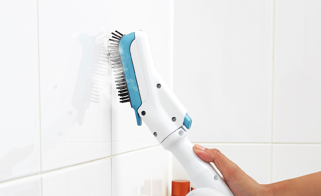 Someone using an attachment on a steam cleaner to clean shower tile and grout.