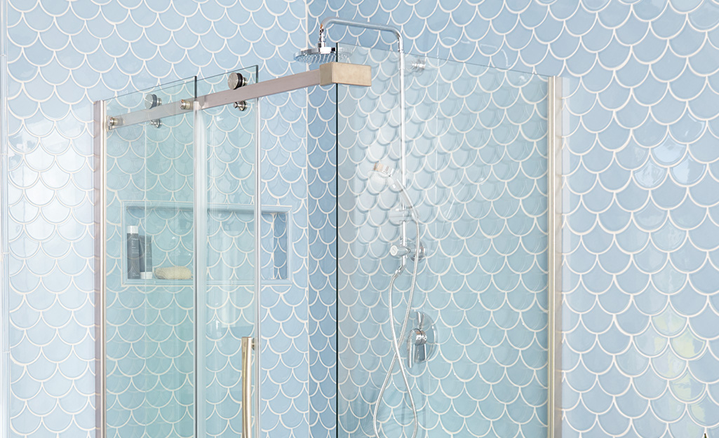 A shower stall with clear, clean glass doors.
