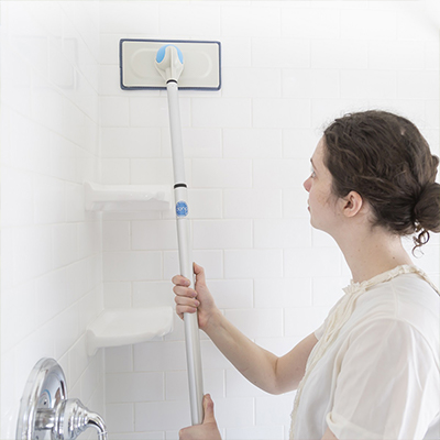 A woman using a long-handled cleaning tool to wipe down a shower wall.