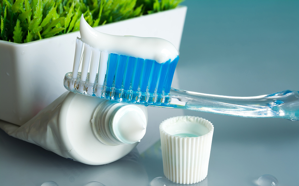 A toothbrush with toothpaste on a table next to a planter.