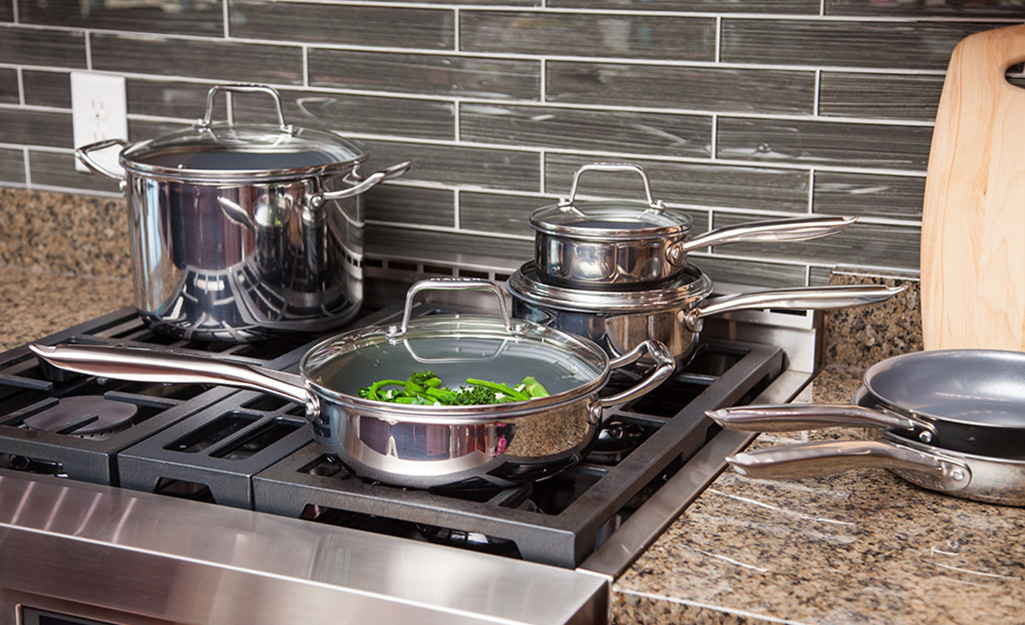 Shiny stainless steel cookware sits on a stove and countertop.
