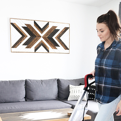 A woman in a plaid shirt pushes a carpet cleaner.
