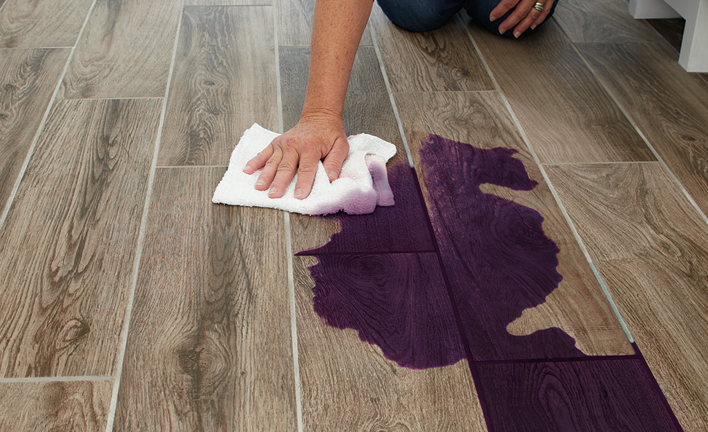 A person using a cloth to clean a spill on a porcelain tile floor.