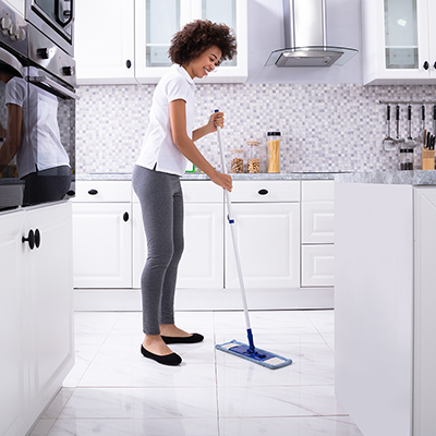 Một người phụ nữ sử dụng cây lau nhà để lau sàn nhà bếp bằng gạch.