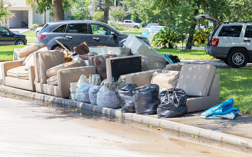 Furniture and other belongings damaged by a flood sitting on a curbside.