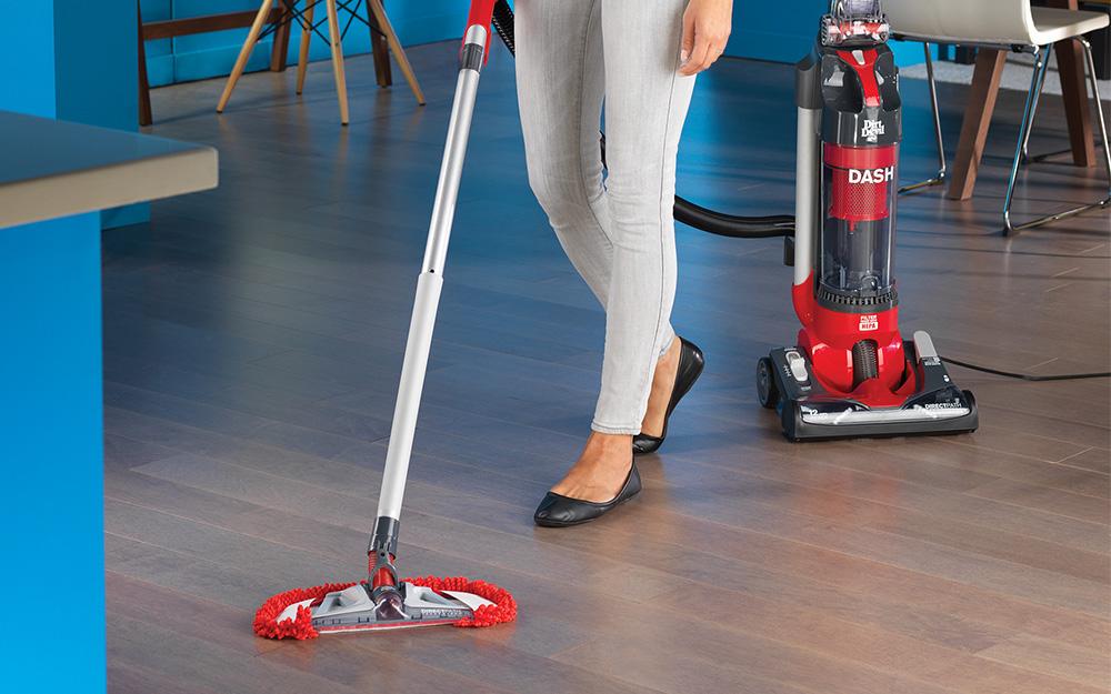 A person mops vinyl flooring
