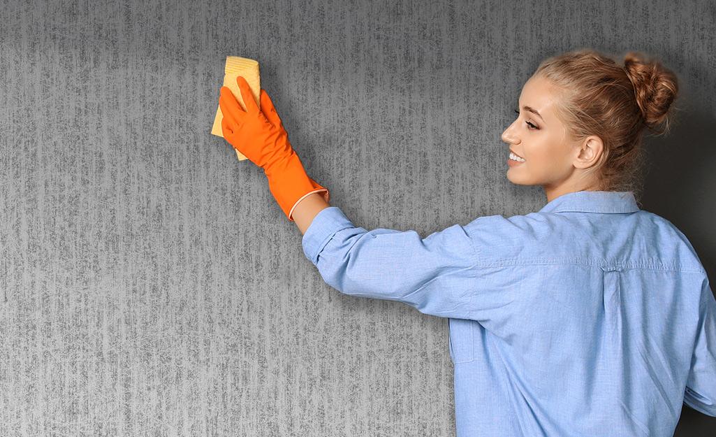 một phụ nữ đeo găng tay để lau giấy dán tường bằng vải